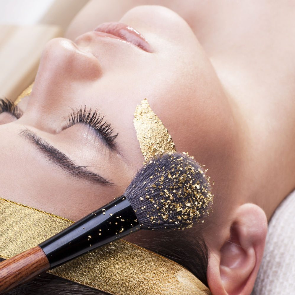 Application of gold cosmetics and skin care in spa.