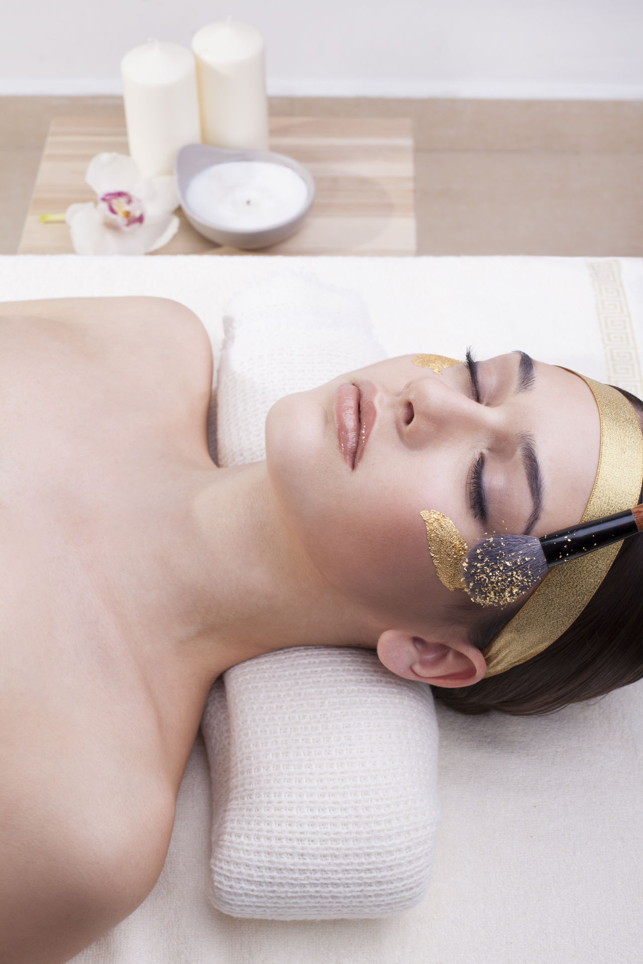 Woman enjoying gold cosmetics and skin care.