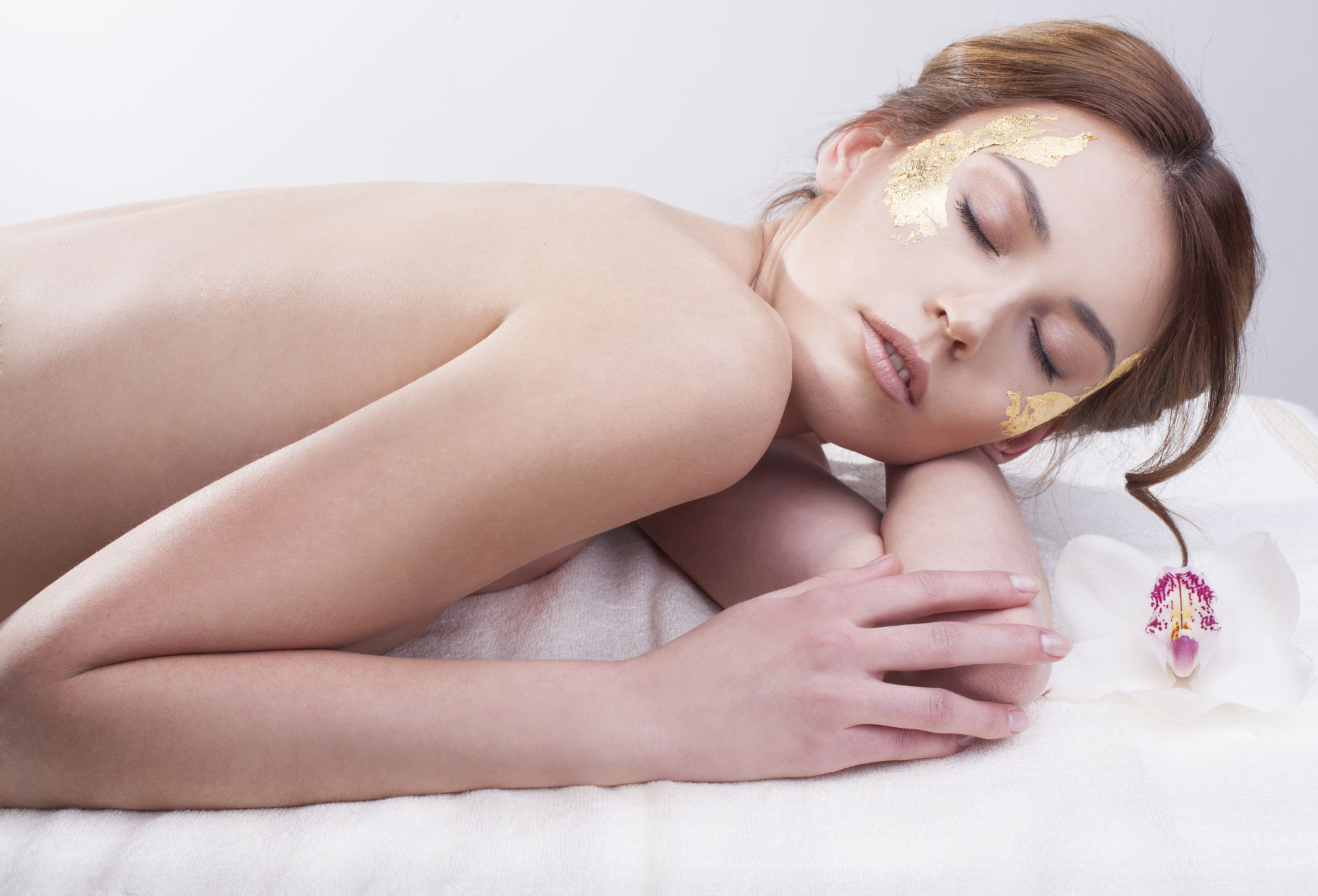 Woman Laying with Gold On Face