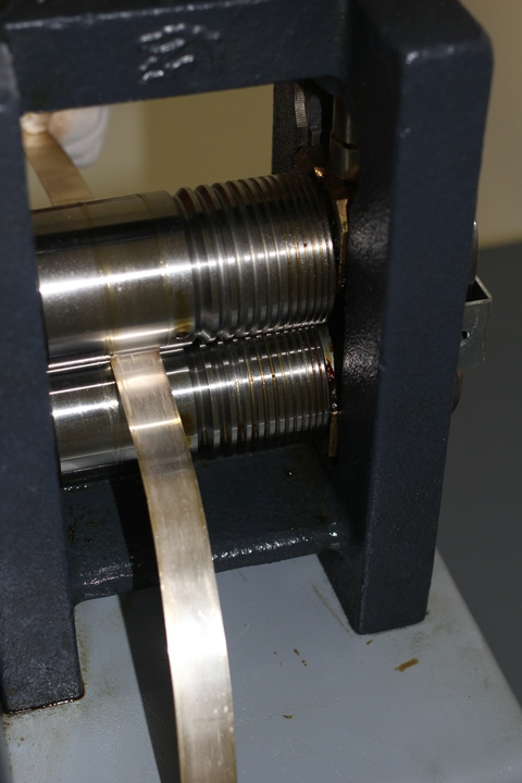 Thin roll of gold comes out of the rolling mill