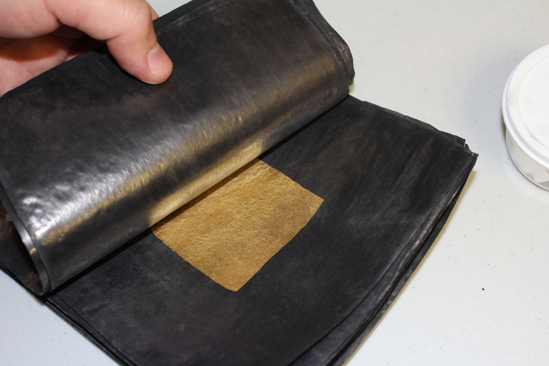 Cut gold sheets are prepared for second beating, put back into black paper.