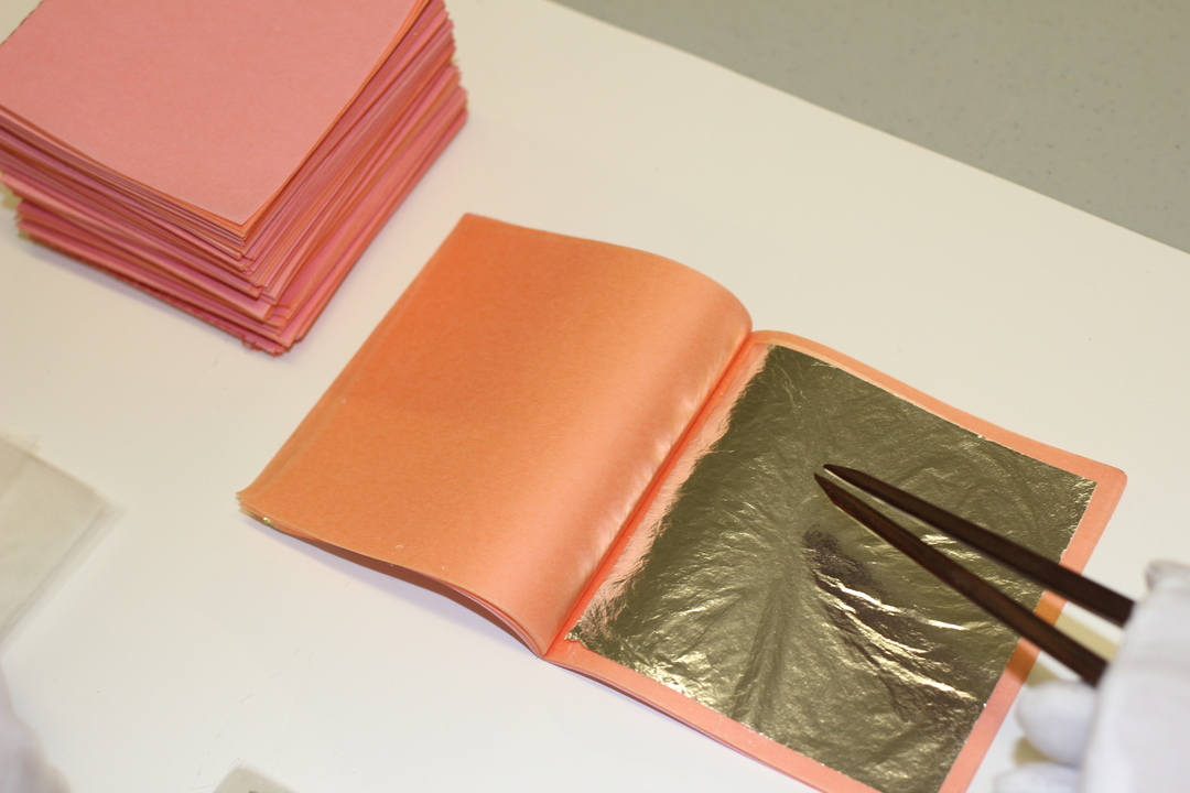 Ready gold leaf sheets are placed into a booklet with care