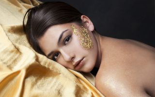 Person laying with gold leaf on skin.