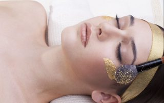 Woman with gold leaf facial mask applied in a spa.
